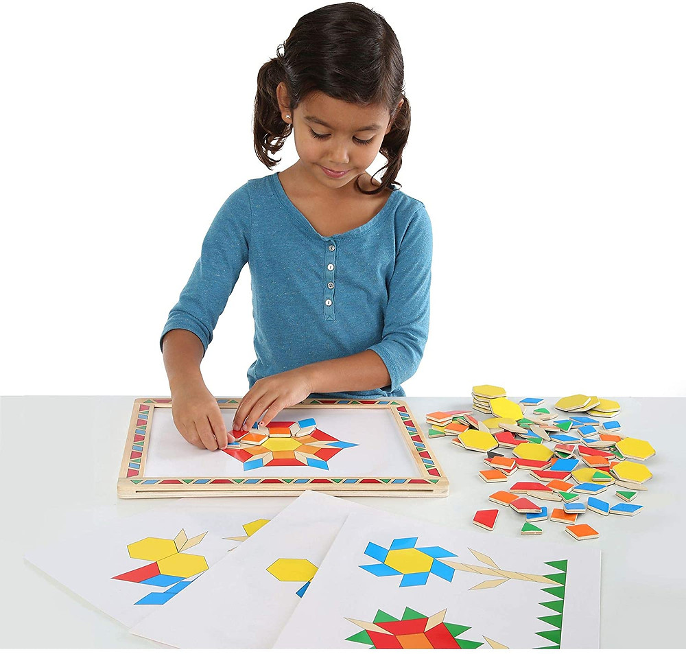 Little girl playing with melissa and doug magnetic pattern blocks