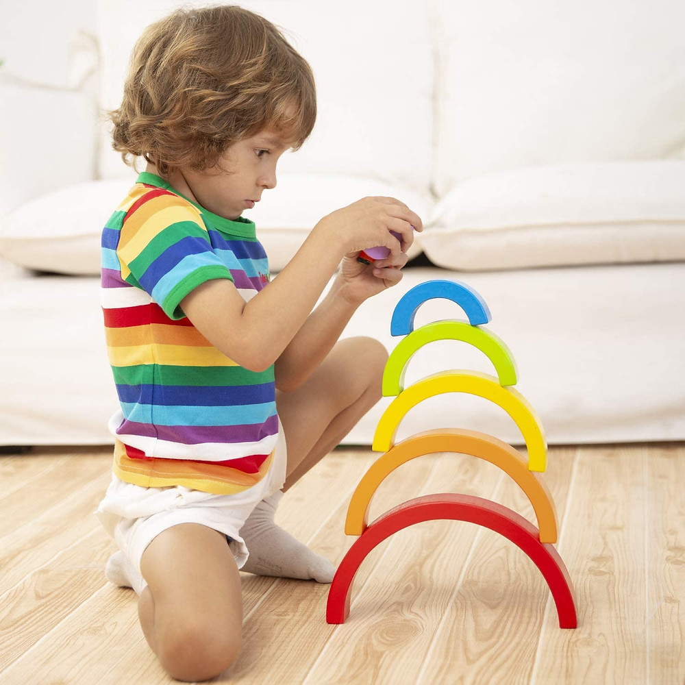 little boy with rainbow shirt concentrating and putting top on rainbow stacking toy