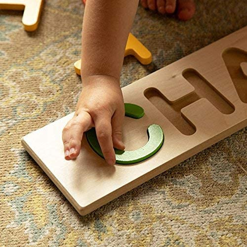 baby hand placing the letter C in a wooden name puzzle