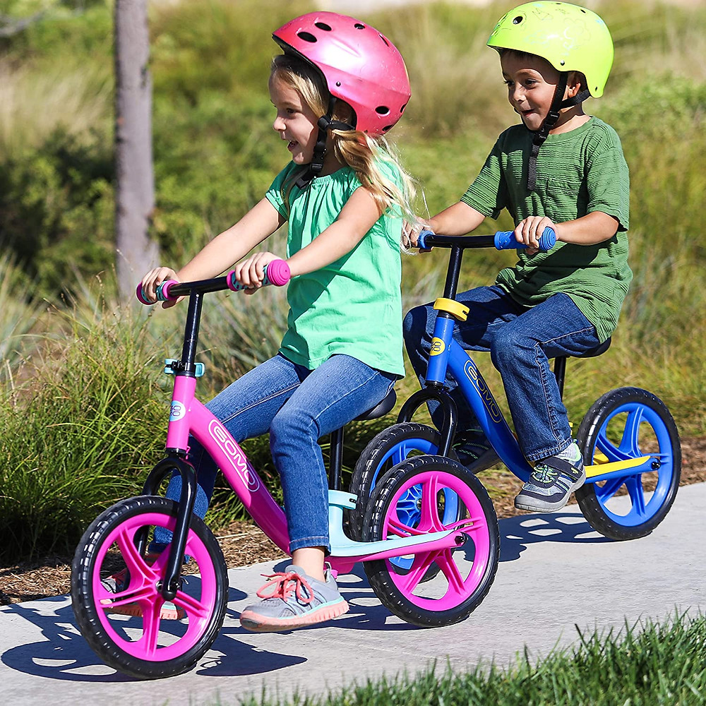 boy and girl having fun riding GOMO balance bikes pink and blue