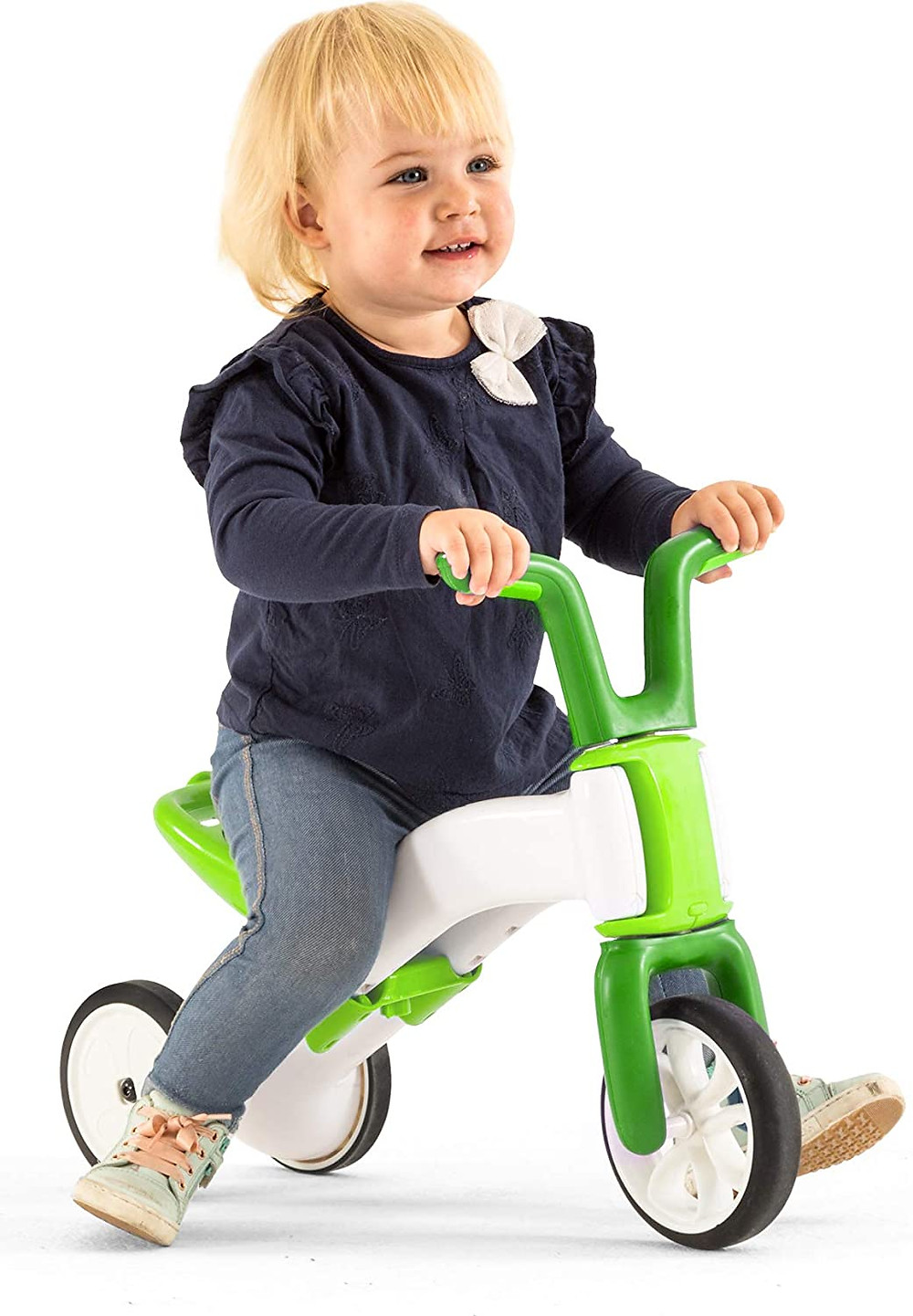 Toddler girl smiling and riding green balance bike