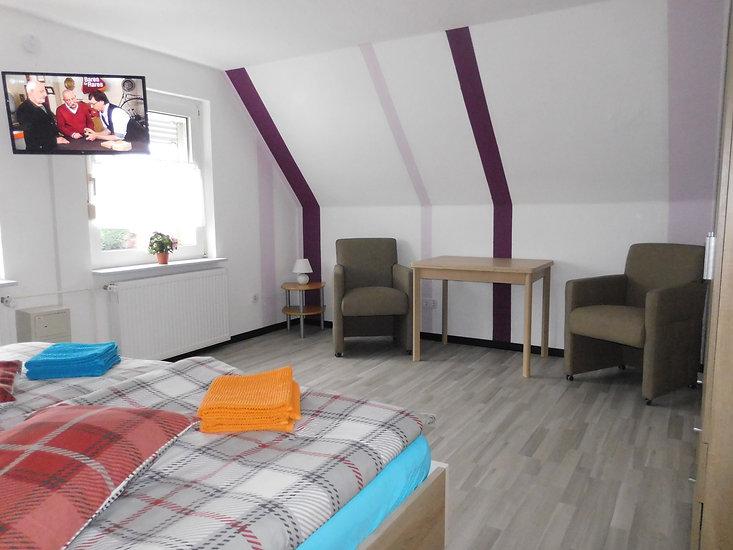 Eine kleine Sitzecke gibt es auch in dem Schlafzimmer der Ferienwohnung Amelsberg in Leer Heisfelde
