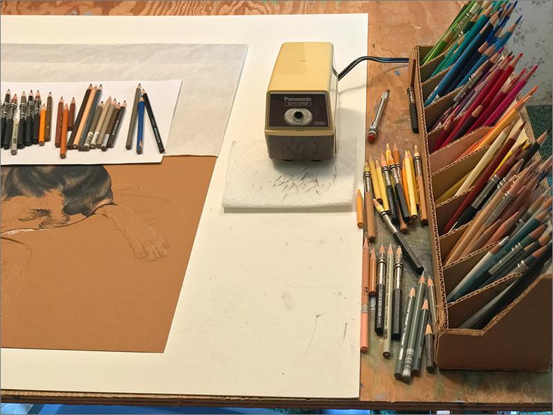 Colored pencil portrait in progress in Kevin's studio with pencil sharpener and colored pencils