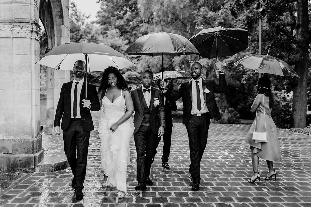 photographe mariage pluvieux paris - mariés et témoins marchent sous la pluie