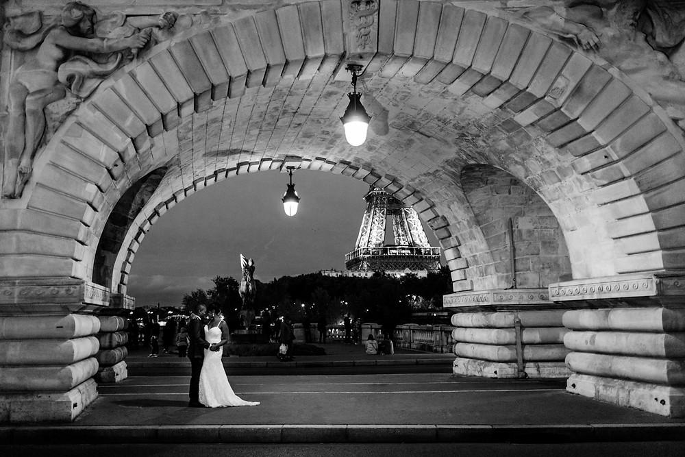 Photographe mariage Paris - portrait des mariés de nuit sous le pont Bir Hakeim