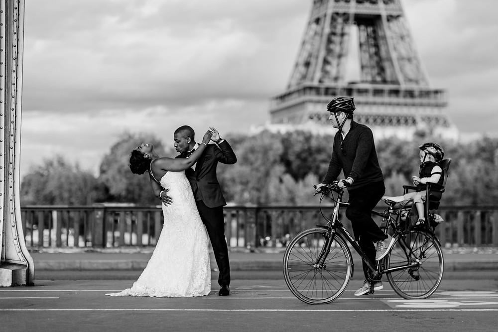 Photographe mariage Paris - couple qui danse sous le pont Bir Hakeim avec vélo qui passe