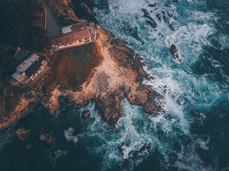 A drone photo taken from above on a rugged shoreline with wild waves smashing into the rocks. On the cliff, a house with a perfect view over the ocean.
