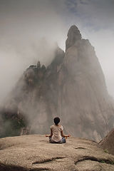 Girl in lotus position in front of a clouded mountain peak. Responsible and safe travel Collab Post.