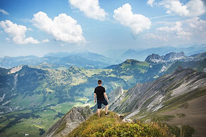 An explorer staring down a slope with breathtaking mountains and a distant valley.