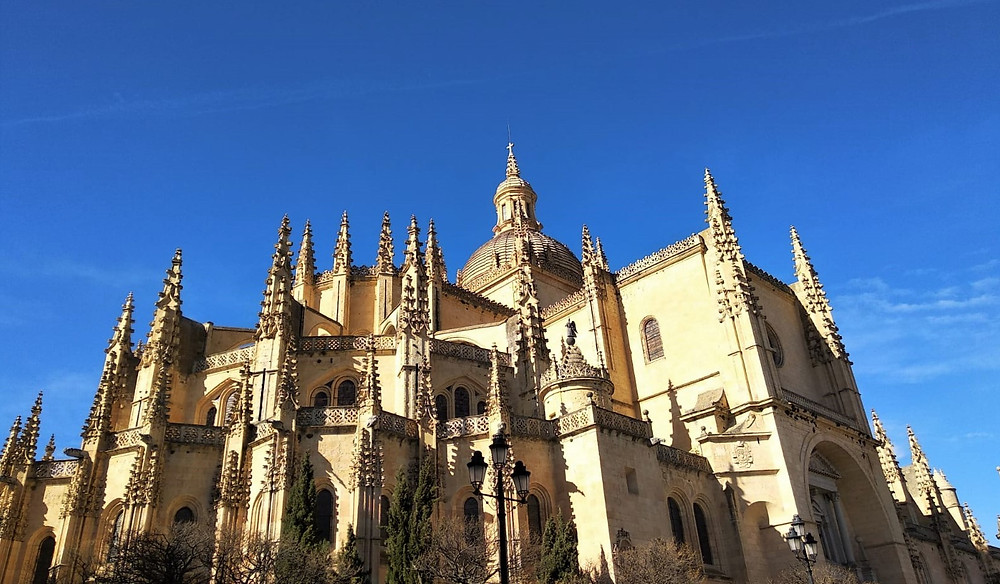 Segovia Cathedral in Spain against a clear blue sky. This is from a Madrid Day Trip Guide on Food and Travel Guides. 4 trips you can take over the day when on vacation in Madrid.