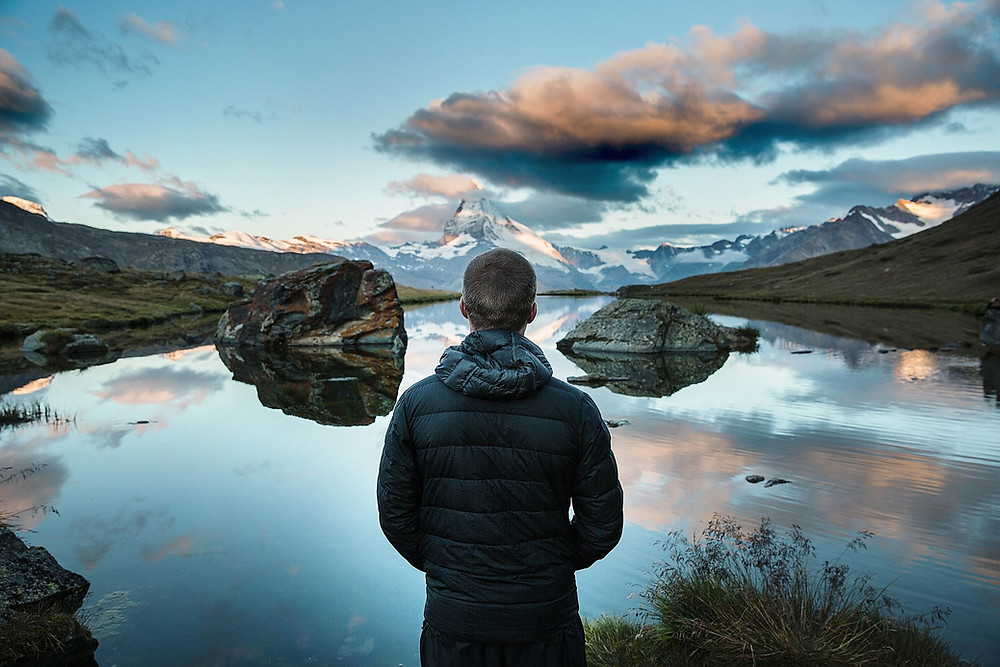 An alone wanderer staring out over a lake on a plateau with a distant snow peaked mountain. Which Food Travel Blogs to follow in 2020? Food and Travel Guides is one of them; nominated on Feedspot. Read about it here.
