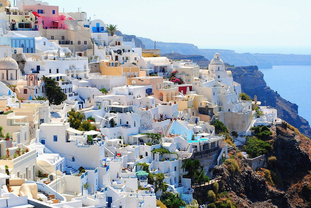 Santorini in Greece is a Top Destination in Europe with white chalked houses; some with blue cupol roofs, climbing up the hills on this Mediterranean Island, surrounded by azur blue waters. An iconic travel destination in Europe high on every travelers bucket list. The greek islands invite you enjoy the greek cuisine and do water activities like sun bathing, sea cruises and water sports.