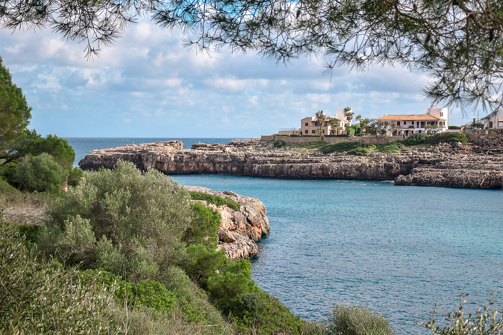 Cala d'Or on Mallorca calm and peaceful little village on Mallorca Island; with picturesque houses along the bay and shoreline. Cala d'Or Beach on Mallorca have charming nature and the village have a relaxing vibe and worth a visit when exploring Mallorca in Spain.