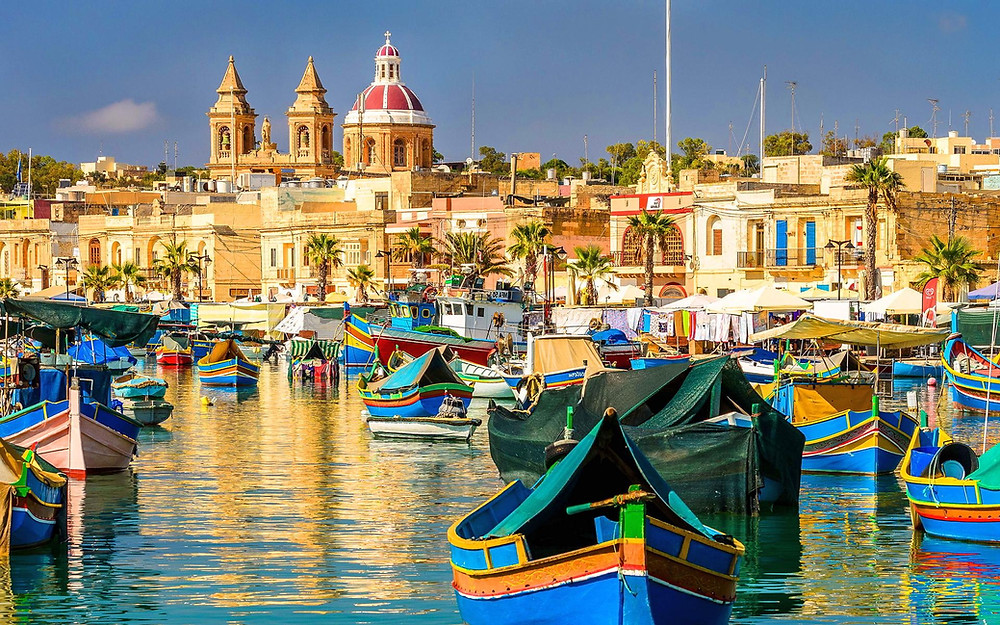A colorful fishing boats lay in a vibrant harbour in the historical parts of Malta. Malta is an island in the Mediterranean Sea with architecture and cultural influences of a combination of Northern Africa, Southern Europe and the Middle East. You'll find a lot of activities, things to do and see on Malta which make the island a perfect destination on your Europe vacation.
