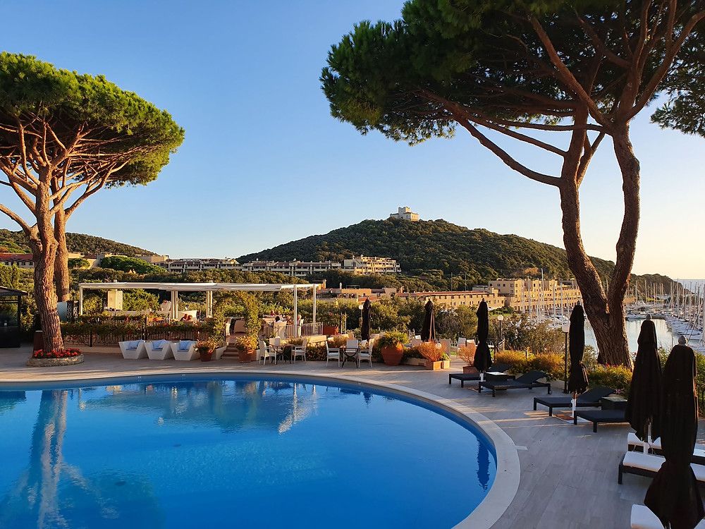 View over the swimmingpool of Baglioni Resort Cala del Porto in Punta Ala. Punta Ala hill and the harbour below in the background with cypress trees surrounding the pool. This European Destination is a must-go when visiting the region of Tuscany in Italy.