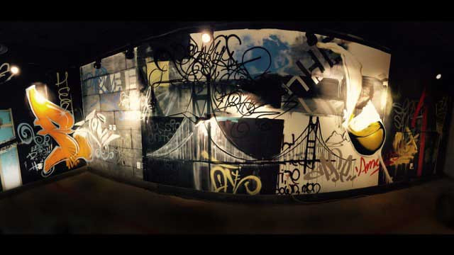 Custom graffiti on a wall: a bridge, glass of wine, and  lettering in one mural