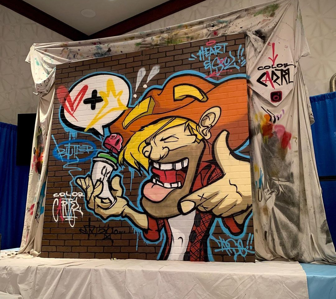 Large graffiti canvas with a brick wall background and cartoon character in bright, contrasting color.