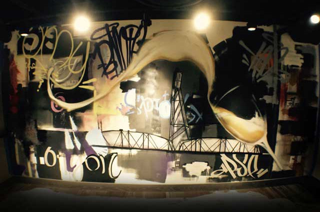 Wall mural from one of the best local graffiti artists: a glass with overflowing wine and lettering