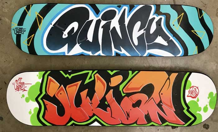 Skateboards decorated with different color palettes by our graffiti artist for hire