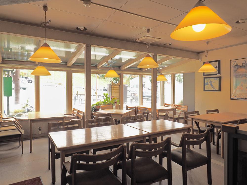 お食事は、大きな窓から外を眺められるテラス風ダイニングで。こぢんまりとした温かみのある会場で地元の家庭料理をお楽しみください。