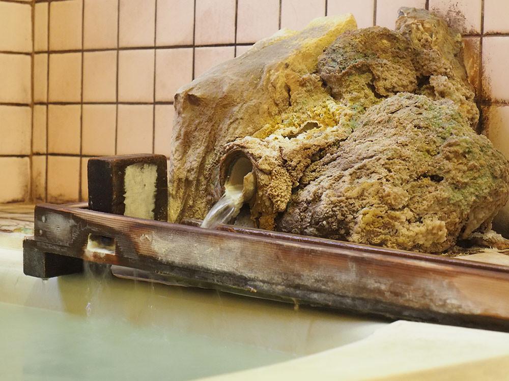 長年使っている湯出口には硫黄がこびりつき、昔から変わらない温泉の特徴をあらわしています。