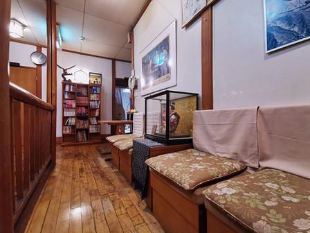 お部屋前の廊下とコミックコーナーです。中央に貼ってある古い新聞広告。そこで笑っているのは…