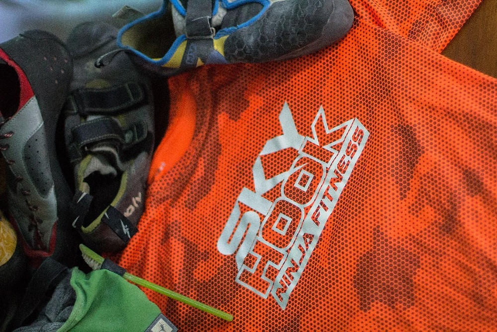 multiple climbing shoes pictured with a Skyhook shirt