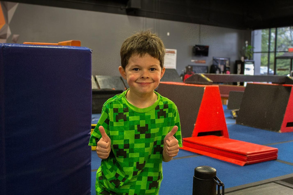 A smiling boy with thumbs up at Skyhook Ninja Fitness