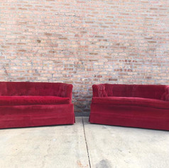Worn red tufted velvet loveseats
