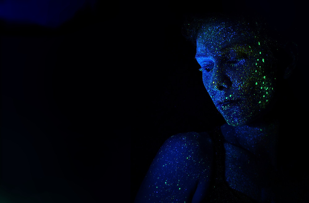 Photo by H. Heyerlein of woman with neon speckles painted on her face with a black background