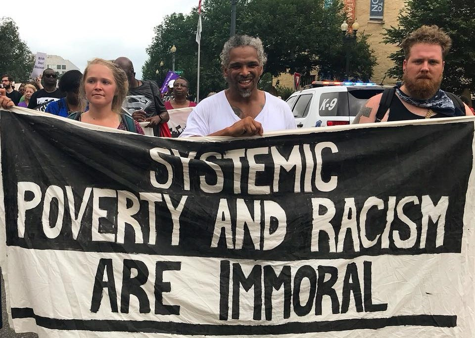 """Photo of Micah and other activists holding a sign that says, """"Systemic Poverty & Racism Are Immoral"""""""