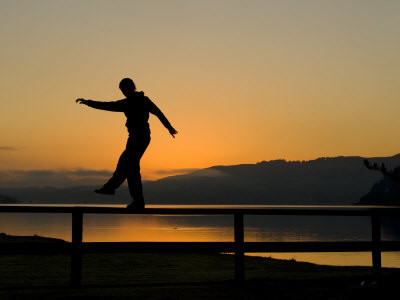 Man doing a balance walk on a fence with a sunset background.