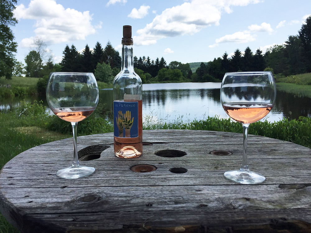 Wine glasses and bottle next to pond