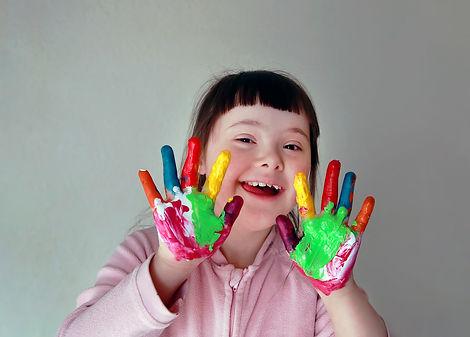 Niña con Down muestras sus manos pintadas