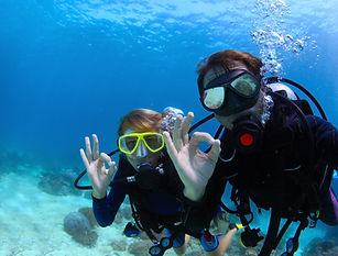 Scuba divers underwater showing ok signa