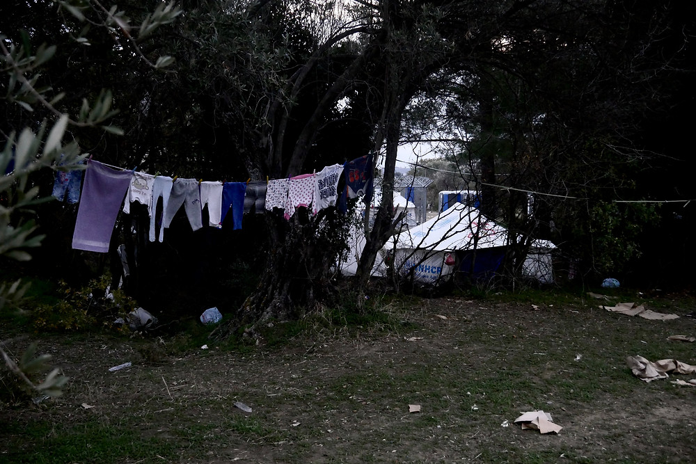 Clothes hung up to dry among tents in the forest.