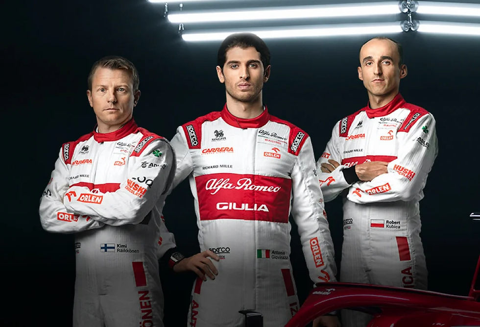 Image showing three men in racing uniforms standing face forward. The middle man has his hands by his sides, the other two are crossing their arms.