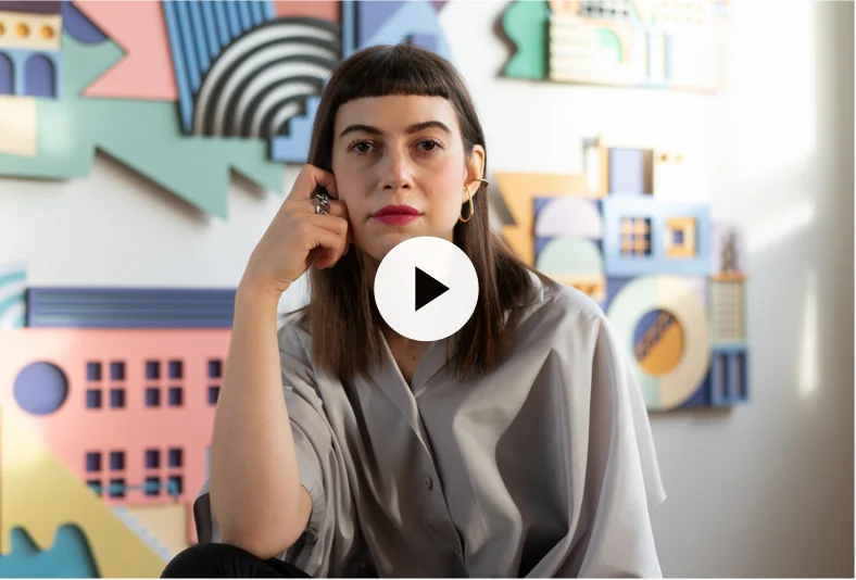 Portrait image of designer Leta Sobierajski resting one hand on the side of her face, sitting in front of colorful graphic wall art.