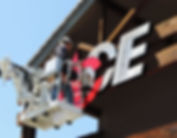 worker installing an electric sign on a building
