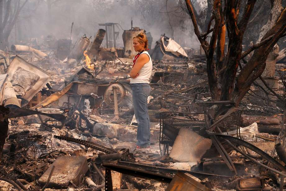 Person, presenting as female, standing in smoldering remains of burned homes