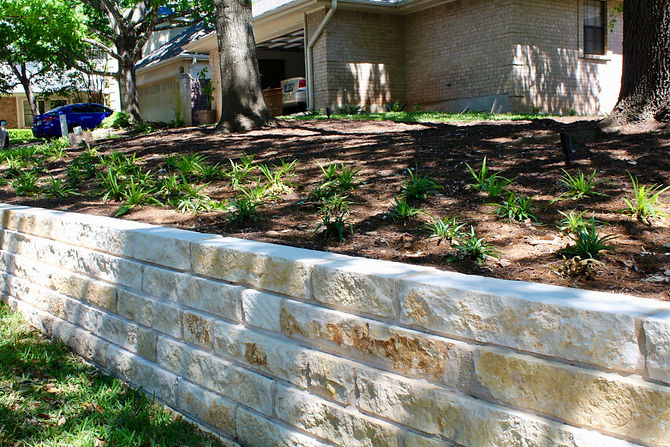 This client came to us because the HOA said he had to do something about the soil in his yard eroding onto the street. Because he had some plumbing done, the yard was completely dug up and there was not much grass left. Additionally, all the plants around the house were old and dated and needed to be replaced. In the end, we came up with a terracing plan that used steel and boulders along with limestone block walls. We then reduced the height of the walls on either side of the entry stairs to make it more inviting. Lighting was added to the entry for night time use. The plantings around the front entry were arranged to try to give as much symmetry as possible to the asymmetrical house.