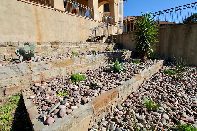 This client came to us wanting to add plants to their beds. When the wife mentioned that she hated the limestone cliff in their front yard, we decided the best thing to do would be to build up the cliff and add beds above it. We constructed a limestone wall with boulders, incorporating several cubbies to add plants. Down the wall, we also added various varieties of plants to spread across the bed along with some large yuccas, trees and succulents.