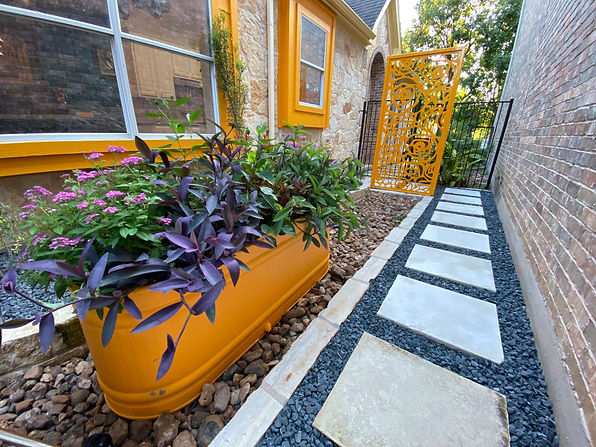 This client is the mayor of Sunset Valley. She wanted to accomplish two goals, creating a more useable space in the front yard for her family and dogs to spend time in and preventing town members from knocking on her front door when they have requests. We created a plan with a fence around the front, expanded some bed areas, added a small seating area and incorporated some modern design elements mixed with her love of flair.