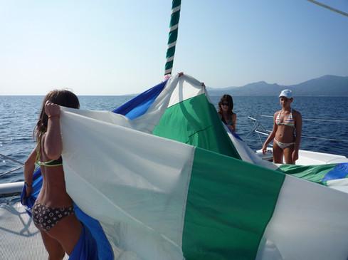 Préparation du spinnaker, pliage de la voile pour son envoi, beaucoup mieux qu'une simple promenade en mer, la découverte de la voile en étant les acteurs de votre escapade en mer.