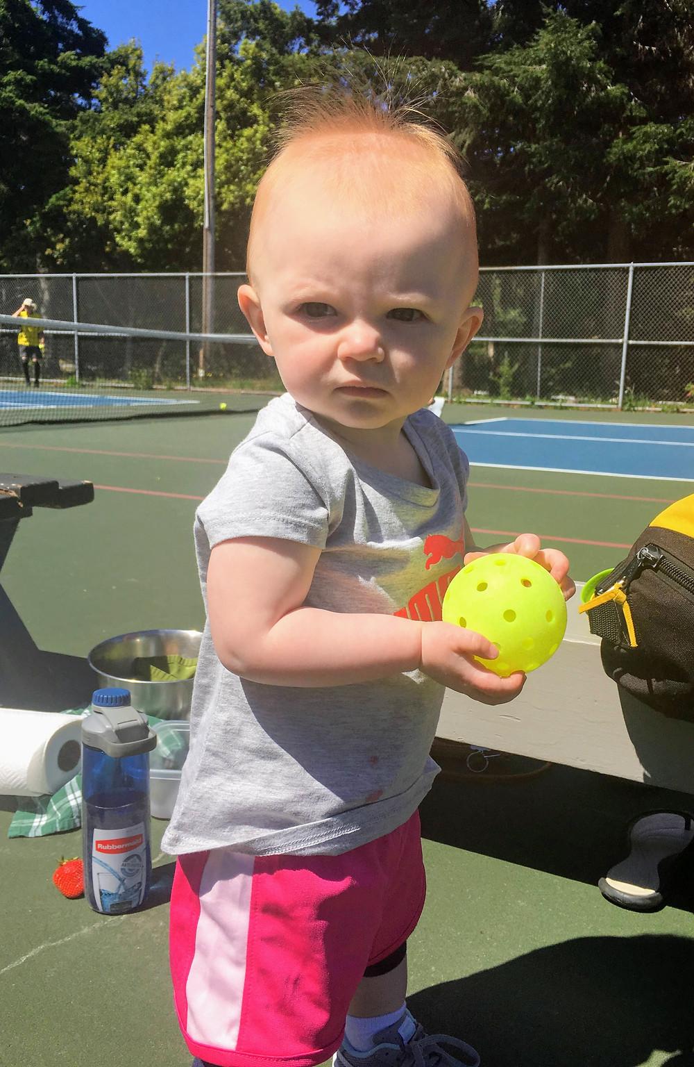 Little girl holding pickleball.
