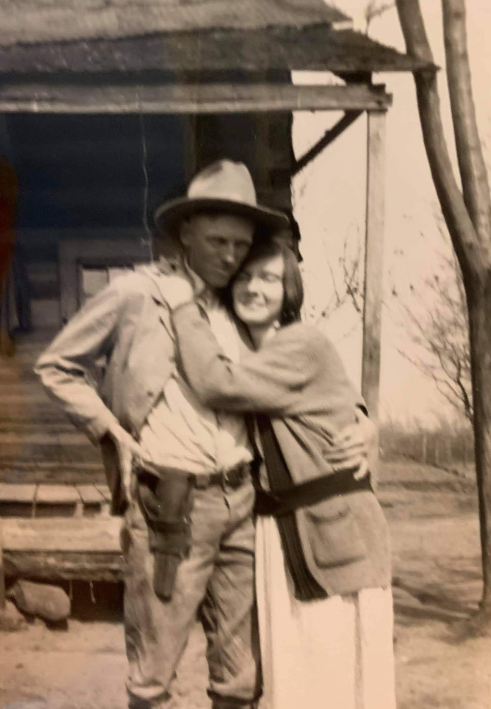 Historic photo of loving couple on East Texas farm. Man has sidearm in holster. Woman hugging man at old farmhouse.
