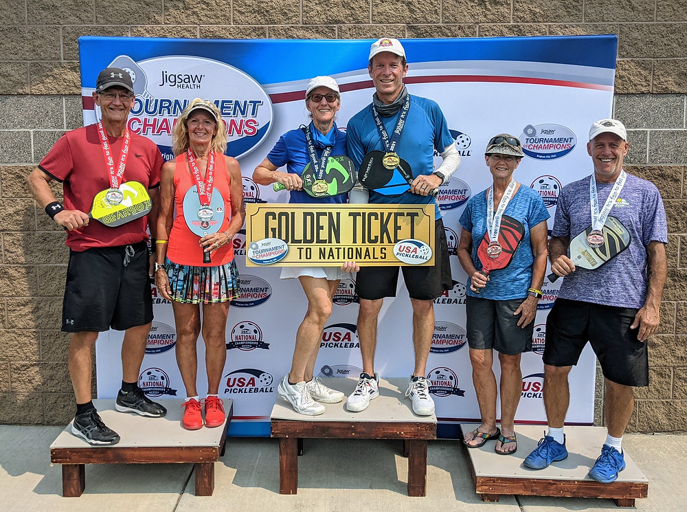 Pickleball tournament competitors Ky and Bonnie Coffey on podium with a Golden Ticket to Nationals