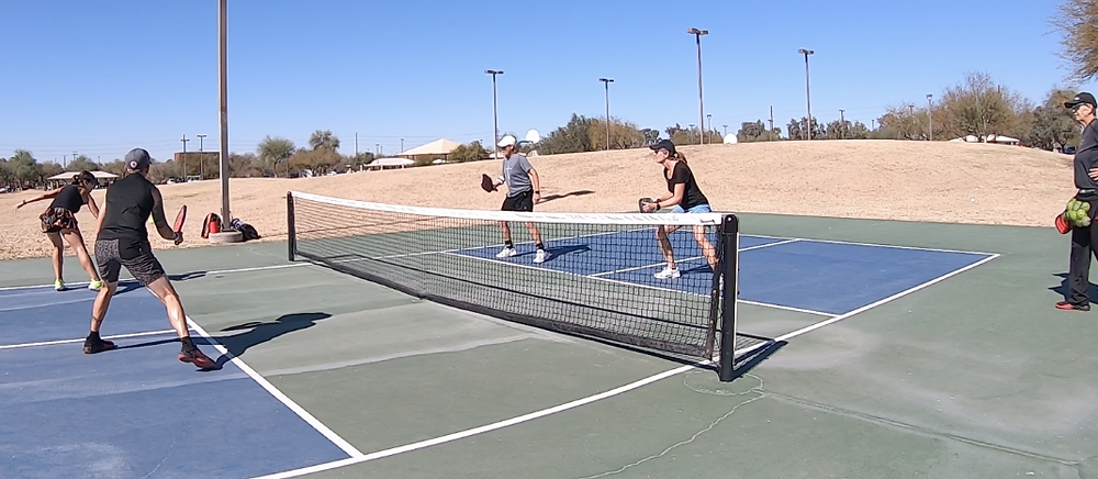 Four women playing pickleball and getting a lesson from Helle Sparre.