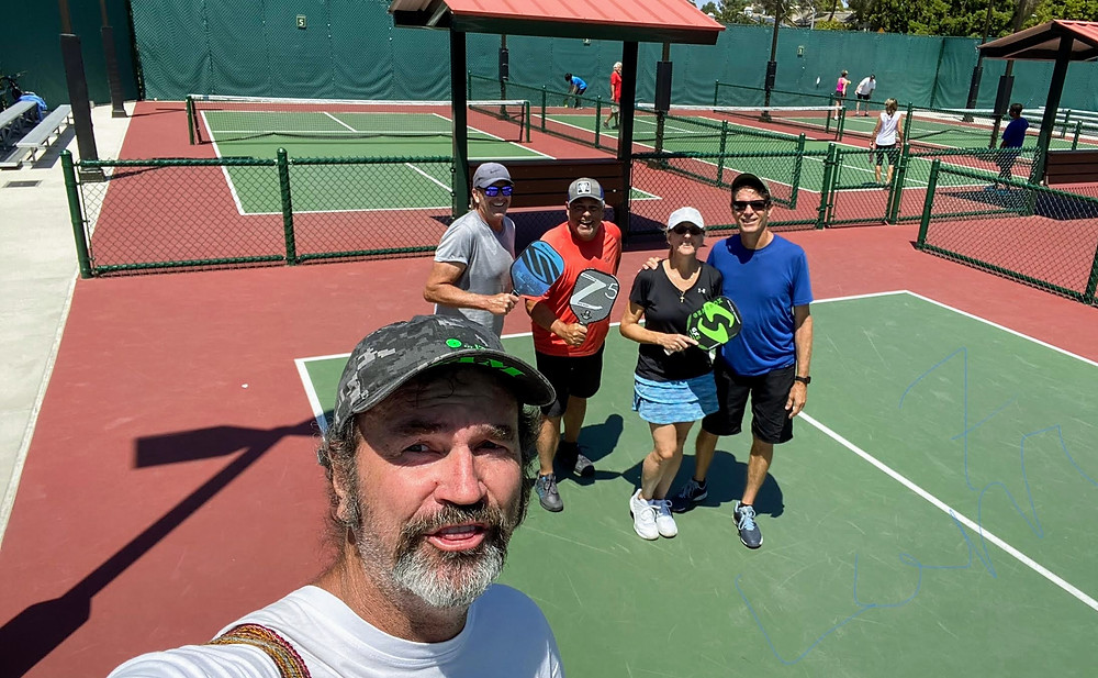 Seven foot man taking photo of pickleball players in Carlsbad, CA