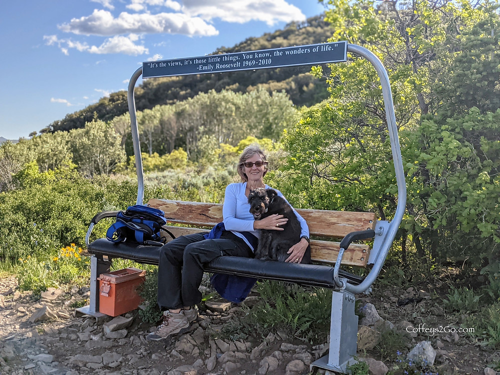 Bonnie Coffey on Emily's Bench in Pinebrook Park City Utah with Basie the dog on a hike